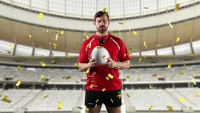 Professional rugby player standing in front of a stadium with confetti falling. Animation of a Caucasian male rugby player playing with a ball and looking to stock video footage