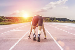 Professional runner taking ready to start position against bright sunlight. Young male runner taking ready to start position Stock Image