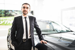Professional salesman smiling in front of a new car Royalty Free Stock Images