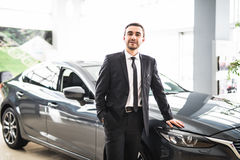 Professional salesman smiling in front of a new car Royalty Free Stock Photography