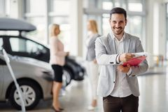 Professional salesperson selling cars. At dealership to buyer stock photography
