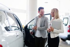 Professional salesperson selling cars at dealership to buyer. Professional salesperson selling cars at dealership to new buyer Royalty Free Stock Image