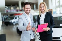 Professional salesperson selling cars at dealership to buyer. Professional salesperson selling cars at dealership to new buyer royalty free stock photos