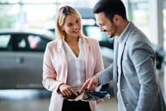Professional salesperson selling cars at dealership to buyer. Professional salesperson selling cars at dealership to new buyer royalty free stock photography
