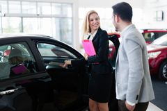 Professional salesperson selling cars at dealership to buyer. Professional salesperson selling cars at dealership to new buyer Stock Photography
