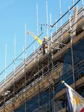 Professional scaffolders at work in London. Professional Scaffolders erect scaffolding to allow the safe maintanance work on a building in London stock photography