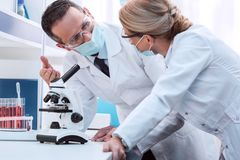 Scientists doing microscope analysis Royalty Free Stock Images