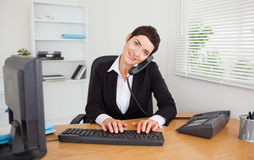 Professional secretary answering the phone. In her office Stock Photography