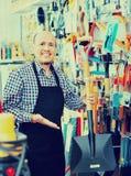 Professional senior salesman offering garden tools Royalty Free Stock Image