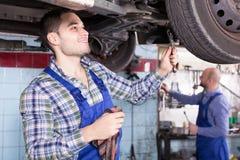 Professional serviceman repairing car Stock Photo