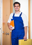 Professional serviceman with tools. Happy professional serviceman with tools standing at doorway and smiling Stock Photography