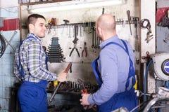 Professional servicemen in repair shop Stock Photo