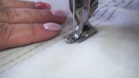 Professional sewing machine, middle-aged woman`s hands stock footage