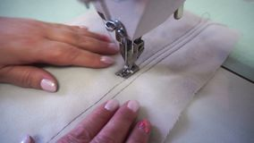 Professional sewing machine, middle-aged woman`s hands stock video