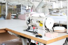 Professional sewing machine overlock in the workshop. Equipment for edging, hemming or stitching clothes in a tailor shop. Fabric royalty free stock images