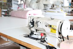 Professional sewing machine overlock in the workshop. Equipment for edging, hemming or stitching clothes in a tailor shop. Fabric stock photos