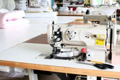 Professional sewing machine overlock in the workshop. Equipment for edging, hemming or stitching clothes in a tailor shop. Fabric stock image