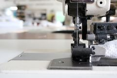 Professional sewing machine overlock in the workshop. Equipment for edging, hemming or stitching clothes in a tailor shop. Fabric royalty free stock photos