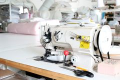 Professional sewing machine overlock in the workshop. Equipment for edging, hemming or stitching clothes in a tailor shop. Fabric stock photo