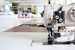 Professional sewing machine overlock in the workshop. Equipment for edging, hemming or stitching clothes in a tailor shop. Fabric stock photography