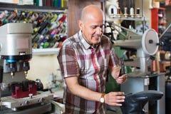Professional shoemaker heeling footwear on machine Royalty Free Stock Photo