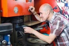 Professional shoemaker heeling footwear on machine. Professional skilled smiling  shoemaker heeling footwear on machine in workshop Stock Photo