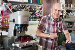Professional shoemaker heeling footwear on machine Royalty Free Stock Images