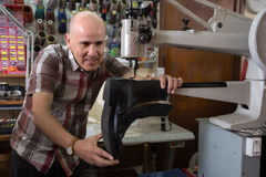 Professional shoemaker stitching footwear on machine in shoe atelier Stock Photo