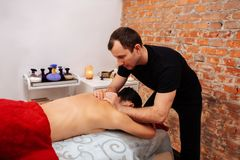 Professional short-haired masseur in black uniform mashing neck of woman stock photo