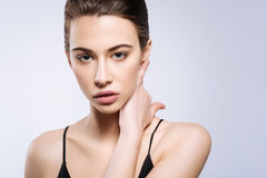 Professional shot of a beautiful model. Beauty on its best. Perfect-looking attractive beginner posing for a photographer while placing her hand on her neck royalty free stock image