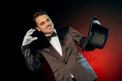 Professional Occupation. Showman in suit and gloves standing isolated on wall making tricks with hat smiling joyful royalty free stock image