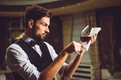 Professional sight at glass of crimson wine. Liquor critic is taking wineglass with red nectar on white napkin and looking attentively Stock Image