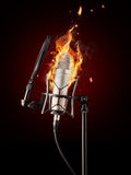 Professional singing microphone in fire. Professional singing microphone burning on black background Royalty Free Stock Photo