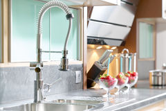 Professional single lever faucet in modern kitchen. Professional single lever faucet in a modern, private kitchen Royalty Free Stock Photo