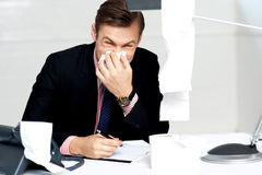 Professional sitting at desk sneezing into tissue Stock Photos