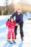Professional ski instructor is teaching a child to ski on a sunn Royalty Free Stock Photo