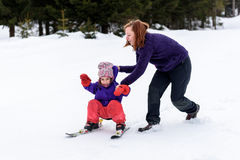 Professional ski instructor is teaching a child to ski on a sunn Royalty Free Stock Images