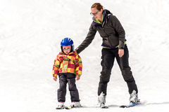 Professional ski instructor is teaching a child to ski on a sunn Royalty Free Stock Photography