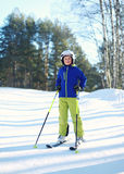 Professional skier child boy in sportswear helmet on ski winter, snowy day on hill mountain over forest Stock Image