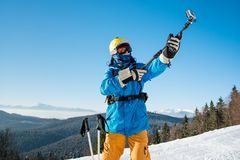 Male skier using selfie stick taking photos while skiing. Professional skier in colorful winter clothing taking a selfie with action camera on selfie stick Royalty Free Stock Photo