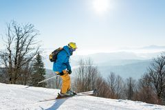 Skier skiing in the mountains. Professional skier enjoying skiing in mountains on a sunny winter day on the winter resort Royalty Free Stock Photography