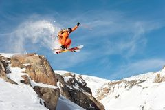 A professional skier makes a jump-drop from a high cliff against a blue sky leaving a trail of snow powder in the Stock Photos