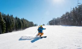 Skier riding in the mountains on a sunny winter day. Professional skier riding down the hill enjoying skiing in the mountains outdoors sport recreation extreme Royalty Free Stock Images
