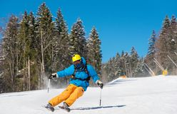 Skier riding in the mountains on a sunny winter day. Professional skier riding down at the winter resort in the Carpathians mountains copyspace extreme Royalty Free Stock Image