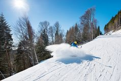 Male skier using selfie stick taking photos while skiing. Professional skier shoting by action camera on selfie stick while skiing on fresh powder snow in the Royalty Free Stock Image