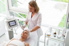 Professional skilled doctor cleansing her clients face. Facial cleansing. Professional skilled doctor using a special device while cleansing her clients face stock photos