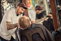 Professional skillful barber shaving beard. On customer Stock Photo