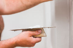 Professional skim coating. Handyman smoothing drywall before painting when renovation the house Royalty Free Stock Image