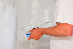 Professional skim coating. Handyman smoothing drywall before painting when renovation the house Stock Photography