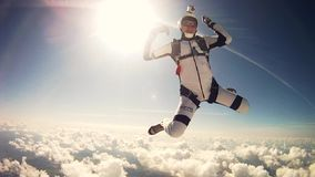 Professional skydivers jump from airplane, freestyle in cloudy sky. Adrenaline.